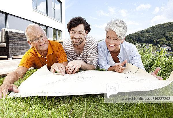 Erwachsener Sohn und Eltern auf dem Rasen liegend mit Blick auf den Bauplan