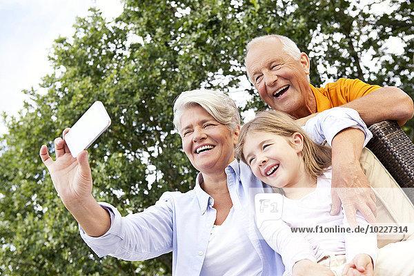 Glückliche Großeltern und Mädchen im Freien  die ein Handyfoto machen.