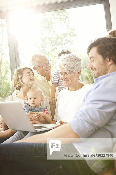 Erweiterte Familie auf der Couch mit Laptop