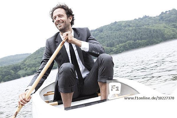 Deutschland  Rur Stausee  lächelnder Geschäftsmann im Kanu