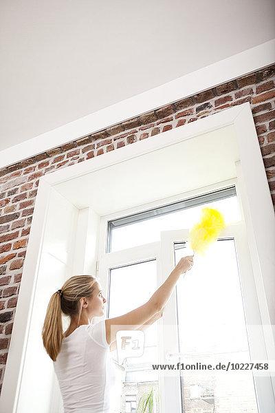 Frau,  die das Fenster abstaubt