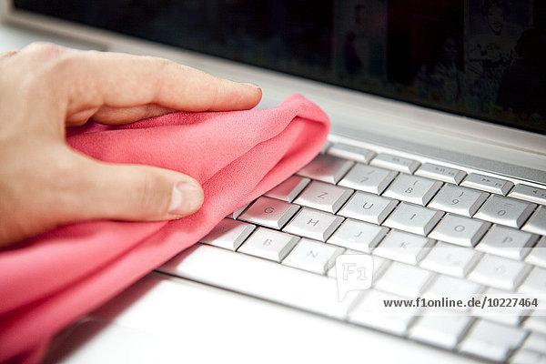 Frau Reinigung Laptop mit Staubwedel