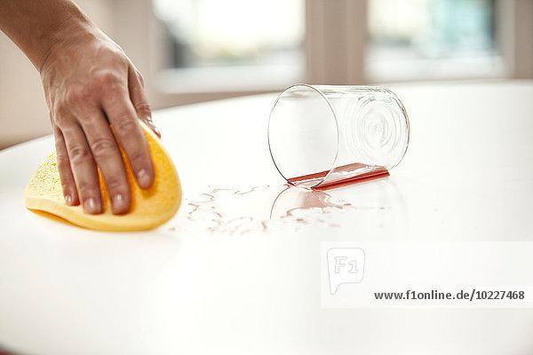 Frau wischt Flüssigkeit vom Tisch vom heruntergefallenen Glas ab