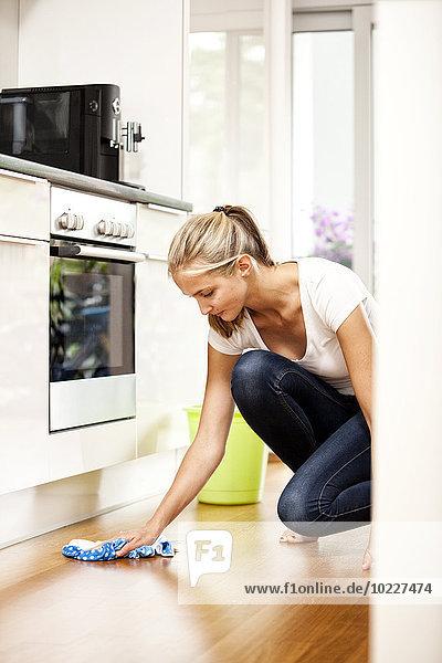 Frau wischt den Boden in der Küche ab
