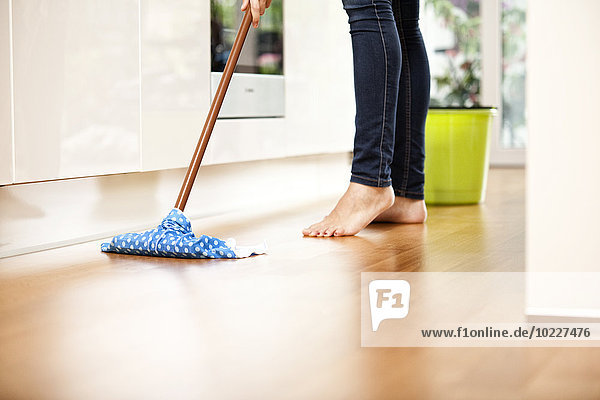 Frau wischt den Boden ab