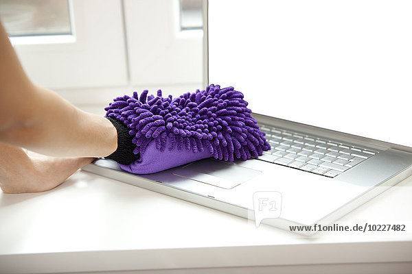 Frau reinigt Laptop auf der Fensterbank