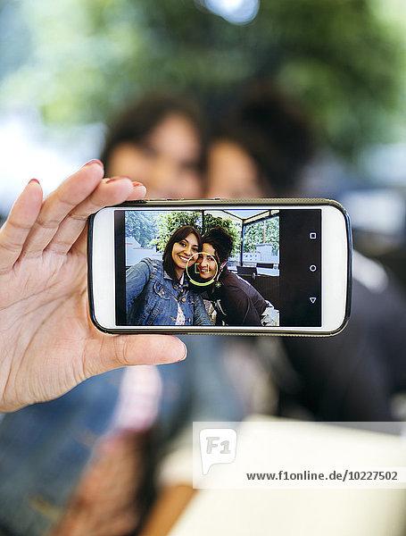 Display des Smartphones mit Fotografie von zwei Frauen  die einen Selfie nehmen.