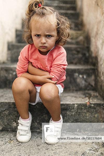 Porträt eines kleinen Mädchens  das auf Stufen sitzt und den Mund schmollt.