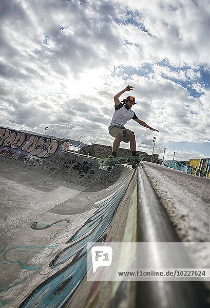 Junger Mann beim Skateboarden im Skatepark