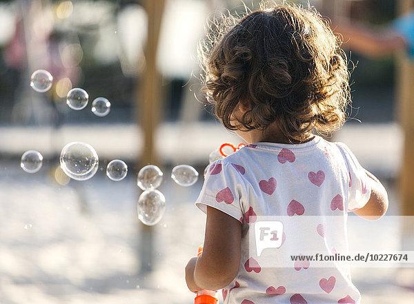 Rückansicht des kleinen Mädchens beim Seifenblasenmachen auf dem Spielplatz