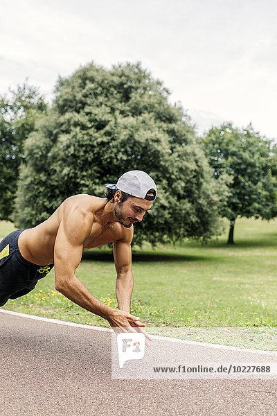 Sportlicher junger Mann beim Training im Park