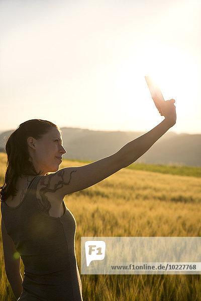 Deutschland  Frau steht bei Sonnenaufgang vor einem Feld und nimmt einen Selfie mit ihrem Smartphone.