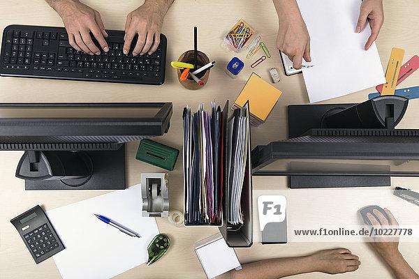 Drei Personen arbeiten auf dem Schreibtisch