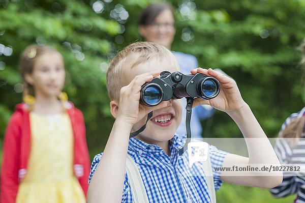 Deutschland  Junge mit Fernglas beobachtet Tiere