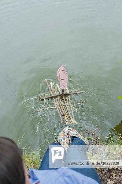 Deutschland  Frau legt Spielzeugfloss ins Wasser