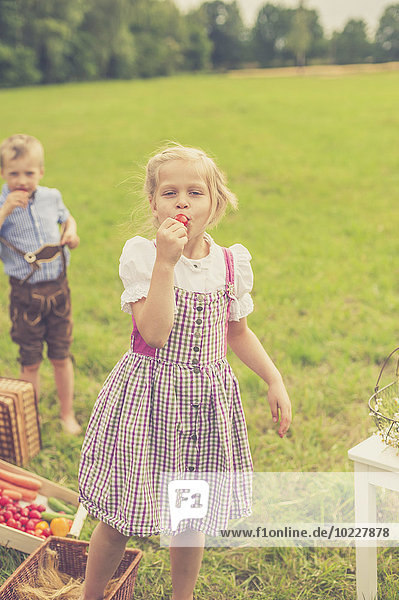 Germany  Saxony  portrait of girl wearing dirndl eating a red radish