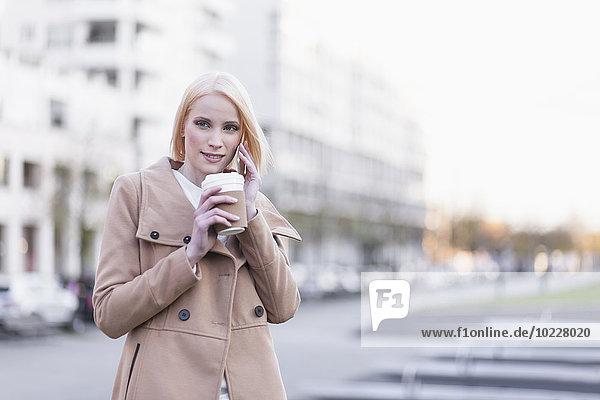 Deutschland  Berlin  junge Frau mit Kaffee zum Telefonieren mit Smartphone