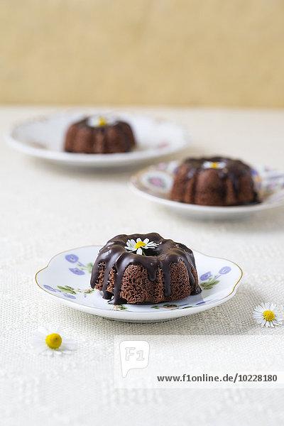 Mini-Schokoladenkuchen mit essbaren Blumen auf Tellern