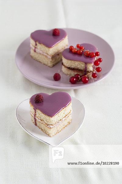 Kleine Kekskuchen in Herzform mit Himbeercreme und Johannisbeergelee
