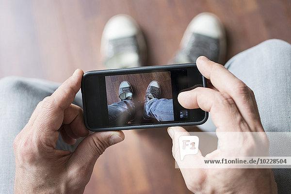 Mann fotografiert seine Schuhe mit dem Smartphone