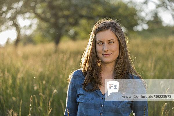 Porträt einer jungen Frau auf einem Feld am Abend