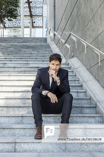 Porträt eines jungen Geschäftsmannes auf einer Treppe sitzend