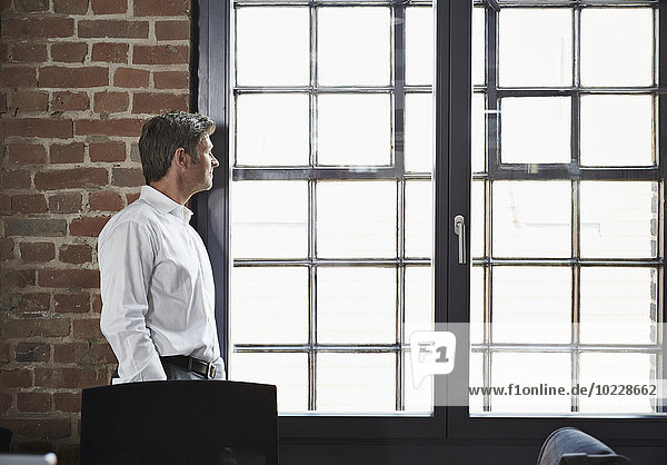 Geschäftsmann im Büro mit Blick aus dem Fenster