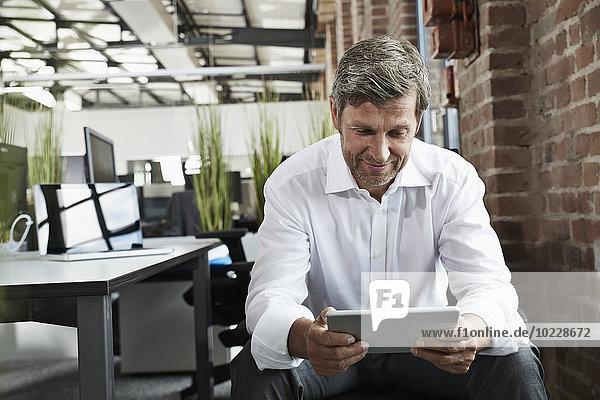 Geschäftsmann im Büro mit Blick auf digitales Tablett