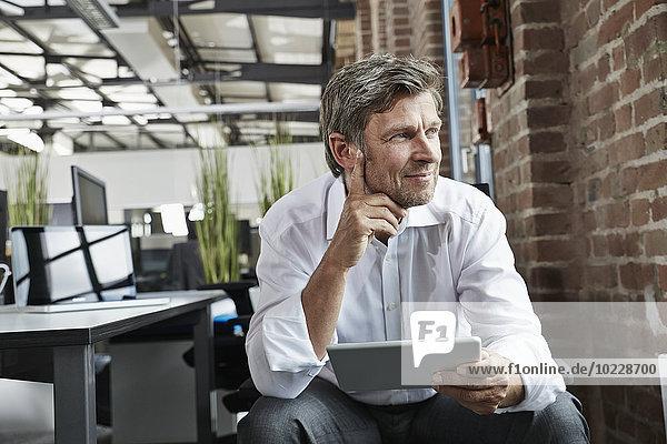 Geschäftsmann im Büro mit digitalem Tablett zur Seite schauend