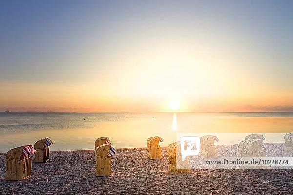 Deutschland  Niendorf  Blick auf den Timmendorfer Strand mit Kapuzenstühlen bei Sonnenaufgang