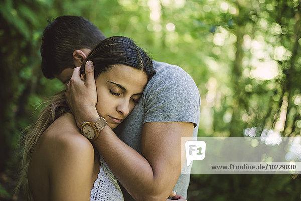 Junge Frau legt ihren Kopf auf die Brust ihres Freundes.