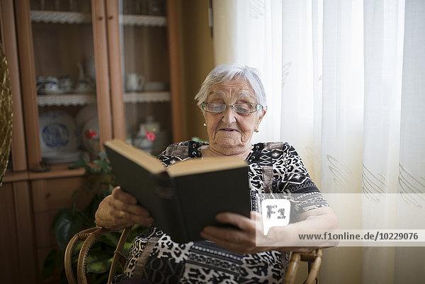 Seniorin beim Lesen eines Buches zu Hause