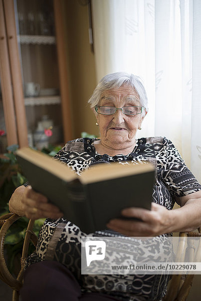 Senior woman reading a book at home