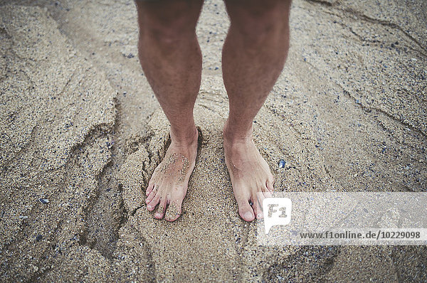 Die nackten Füße des Mannes im Sand am Strand