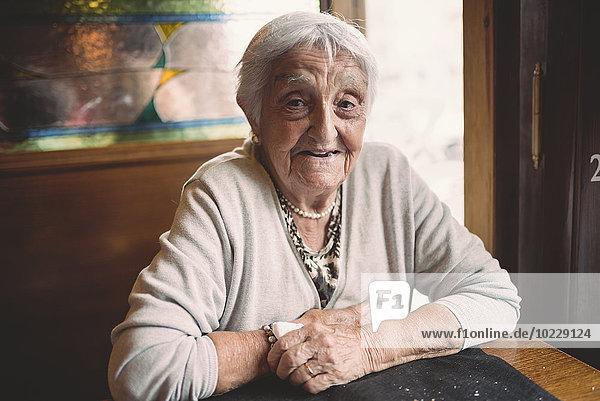 Porträt einer lächelnden Seniorin im Restaurant