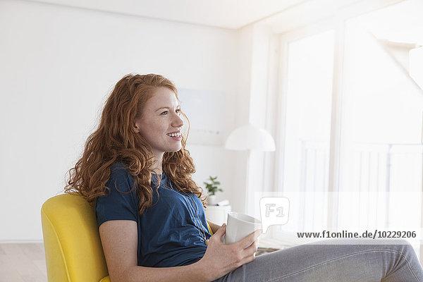 Fröhliche junge Frau mit einer Tasse Kaffee in ihrem Wohnzimmer