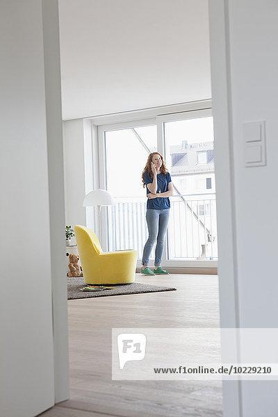 Junge Frau telefoniert in ihrem Wohnzimmer