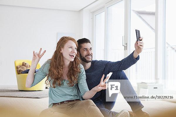 Lächelndes junges Paar  das einen Selfie mit Smartphone im Wohnzimmer nimmt.