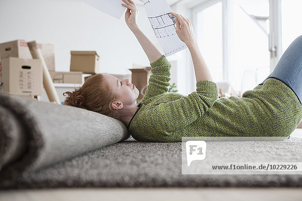 Junge Frau in neuer Wohnung mit Kartons im Grundriss Junge Frau in neuer Wohnung mit Kartons im Grundriss
