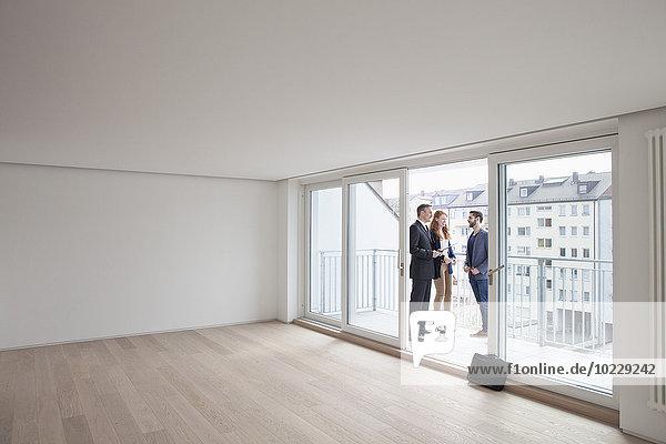 Junges Ehepaar bei der Wohnungsbesichtigung mit Makler