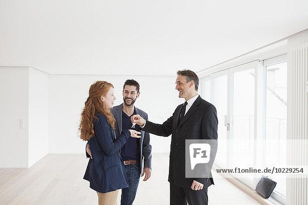 Immobilienmaklerin übergibt Schlüssel an junges Paar
