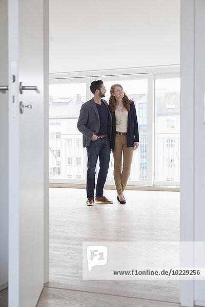 Junges Paar bei der Besichtigung der neuen Wohnung