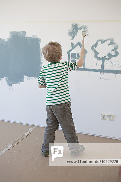 Little boy painting house and tree on wall of his new room