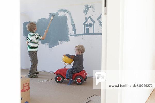 Kleiner Junge malt Haus und Baum an der Wand seines neuen Zimmers Kleiner Junge malt Haus und Baum an der Wand seines neuen Zimmers