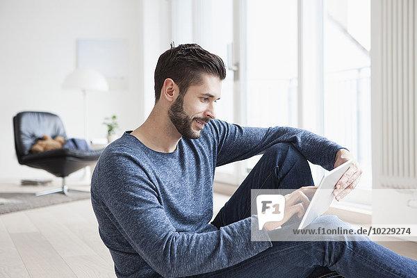 Junger Mann sitzend auf dem Boden des Wohnzimmers mit Mini-Tablette