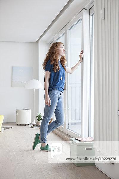 Junge Frau steht in ihrem Wohnzimmer und schaut durchs Fenster.