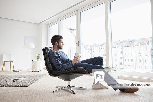 Junger Mann entspannt auf Lederstuhl mit Tasse Kaffee im Wohnzimmer