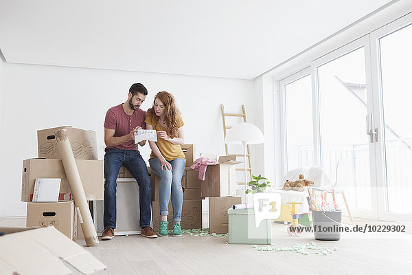 Young couple in new flat with cardboard boxes looking at ground plan