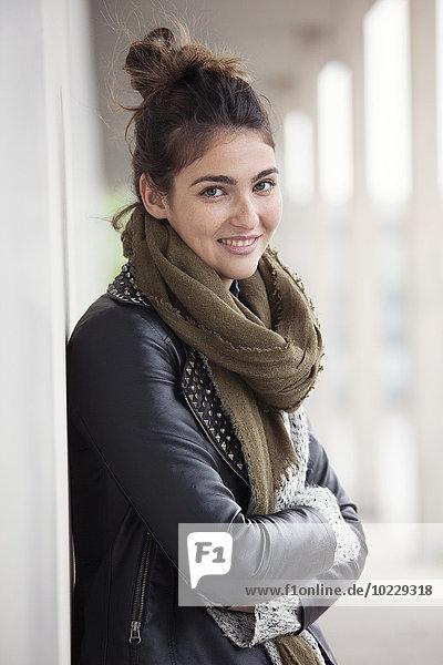 Porträt einer lächelnden jungen Frau mit Brötchen