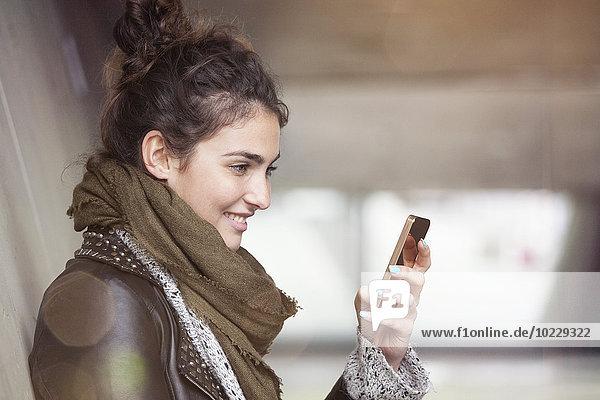 Lächelnde junge Frau mit Smartphone